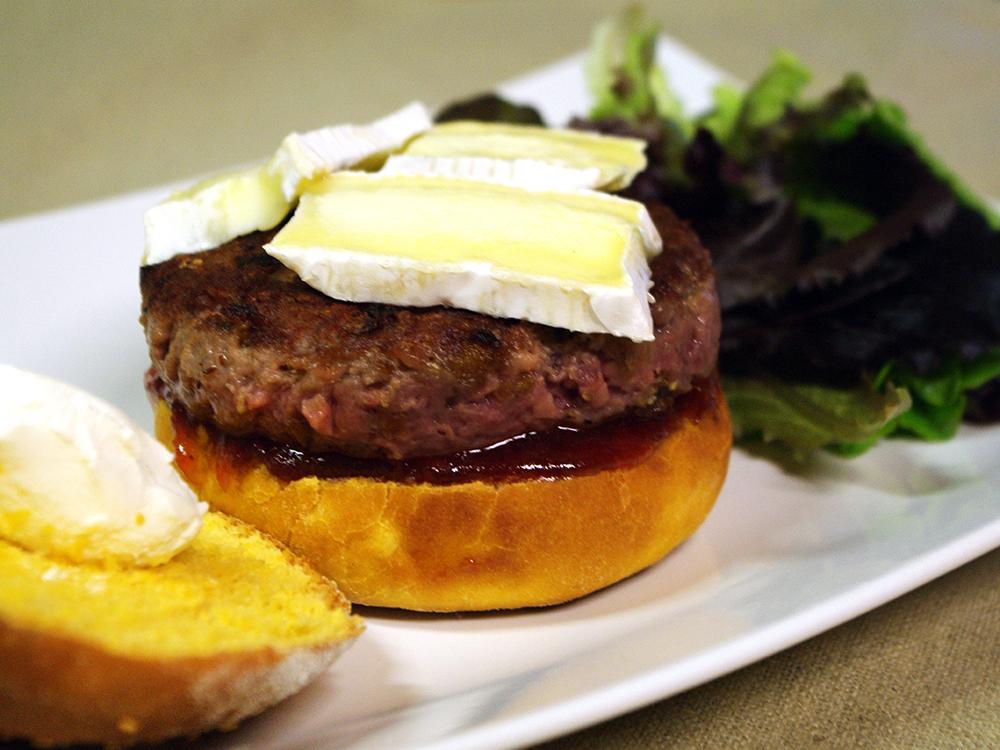 Hamburguesa amb ceba fregida, confitura dolça de tomàtiga i formatges cremós i brie, dins panet de tomàtiga